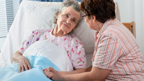 Frau hält die Hand einer älteren Dame, die im Bett liegt