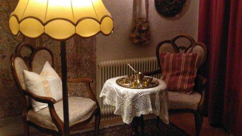 Zwei Holzstühle, ein Tisch und eine alte Leselampe