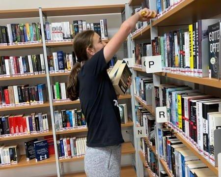 junge Frau am einräumen der Regale in der Bücherei