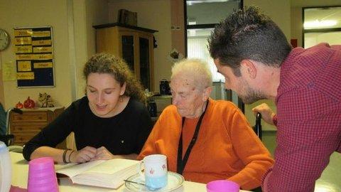 Eine junge Frau liest einer älteren Dame etwas aus einem Buch vor