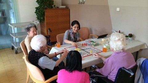 Fünf jüngere und ältere Personen beim Mensch-Ärgere-Dich-Nicht-Spielen an einem Tisch