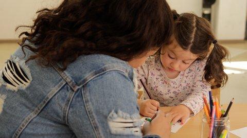 Mädchen und Frau beim Malen mit Buntstiften