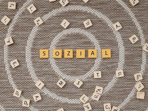 Buchstabensteine gestreut auf einer Spirale, in der Mitte bilden sie das Wort Sozial