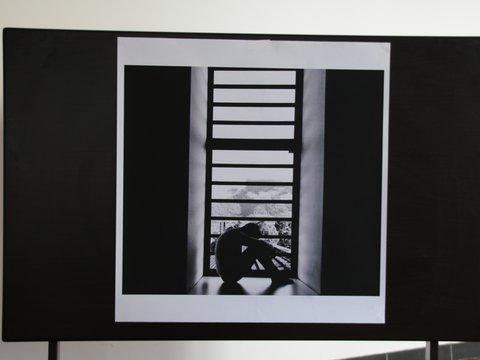 Schwarz-Weiß-Fotografie von einem Mann, der vor einem Fenster zusammengekauert auf dem Boden sitzt
