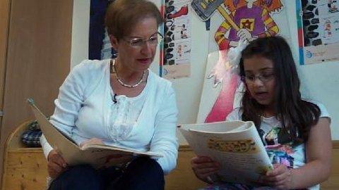 Frau und Mädchen üben gemeinsam lesen