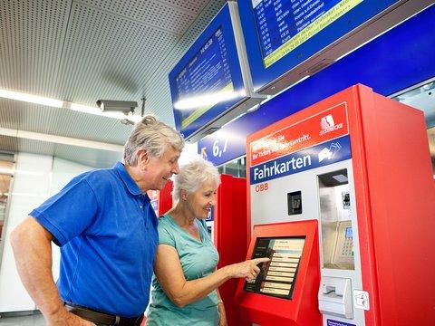 Zwei Personen bedienen einen Ticketautomaten