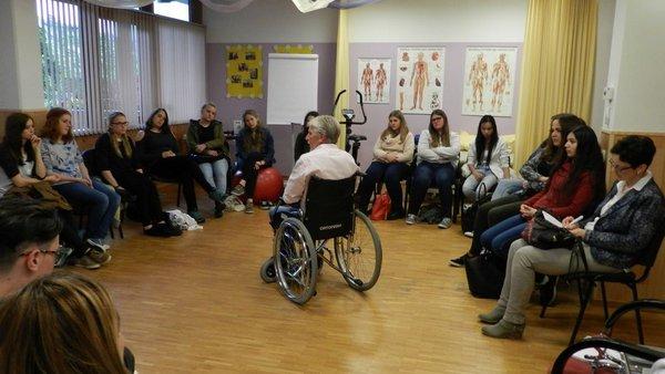 Ein Gruppe von Jugendlichen hören einem Mann im Rollstuhl zu