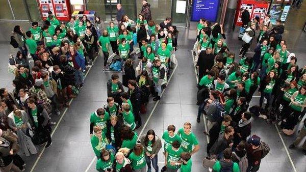 Verschiedene Personen mit grünen T-Shirts stehen auf einem Bahnhofsplatz