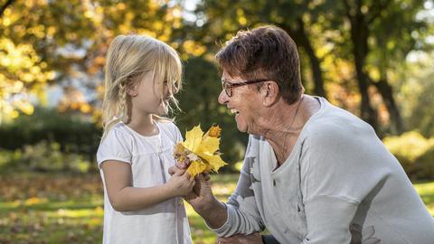 Lächelndes Mädchen mit Oma beim Blättersammeln im Herbst