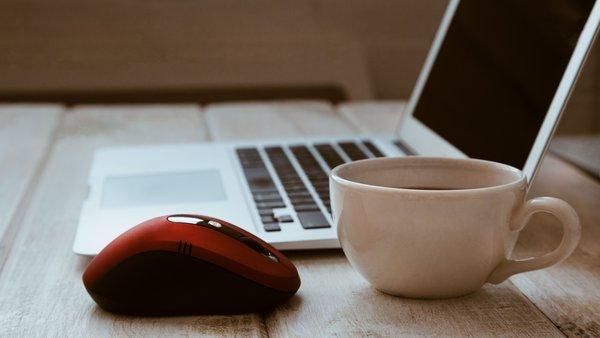Kaffeetasse, rote Maus und Laptop auf einem Tisch