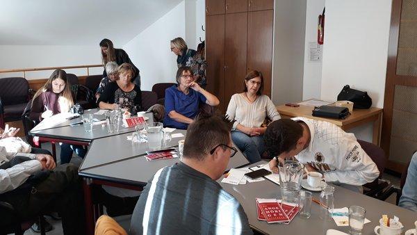Menschen an einem Tisch beim Zuhören und Mitschreiben