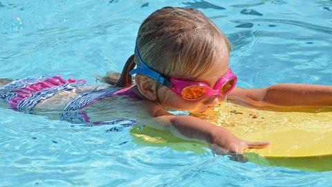 Ein kleines Kind mit Schwimmbrille im Pool beim Schwimmen