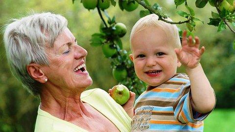 Oma mit Enkel, der einen angebissenen Apfel hält, im Obstgarten