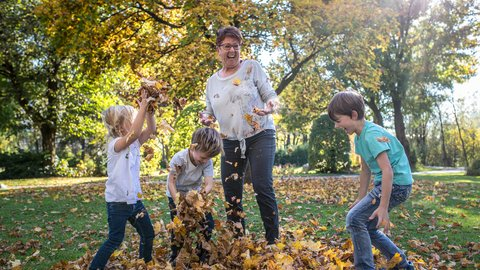 Drei Kinder spielen mit einer Oma mit Blättern im Herbst