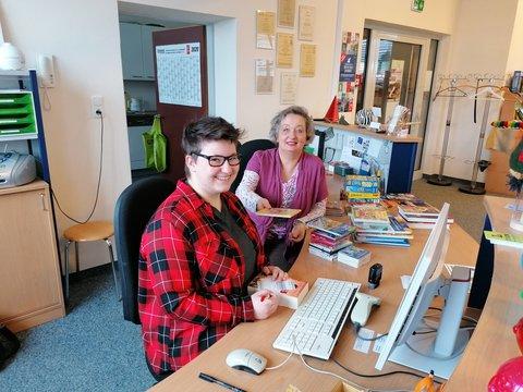 Zwei Frauen in einer Bücherei sitzen am Computer