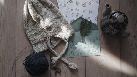 Eine selbstgestrickte Mütze liegt neben einem Brief, einem Wollknäuel und einer Kanne Tee