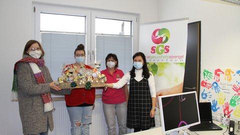 Vier Frauen mit Masken halten einen Präsentkorb mit Adventsgeschenken zu Coronazeiten