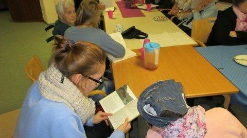 Jüngere lesen älteren Menschen etwas aus Büchern vor