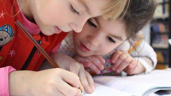 Zwei Mädchen zeichnen in ein Heft