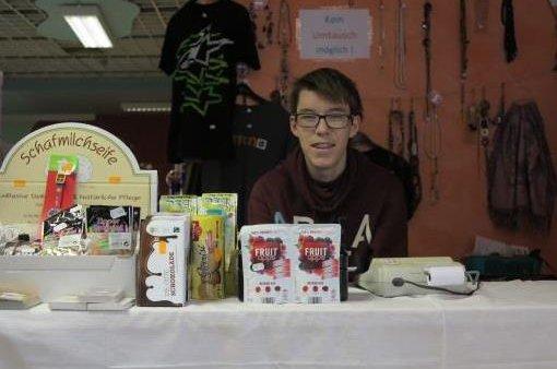 Jugendlicher an einem Stand mit verschiedenen Produkten