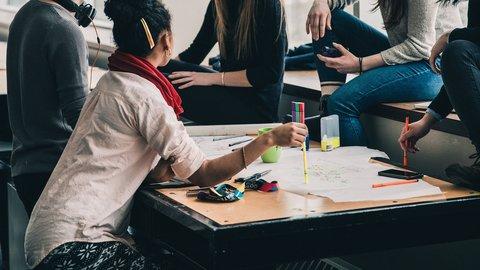 Junge Leute besprechen sich gemeinsam an einem Tisch