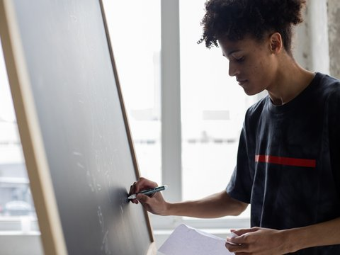 Mann schreibt auf Tafel