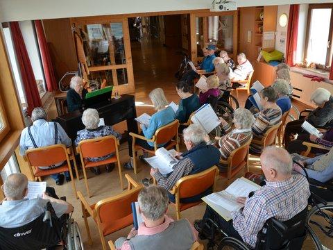 Seniorinnen hören einer Klavierspielerin zu