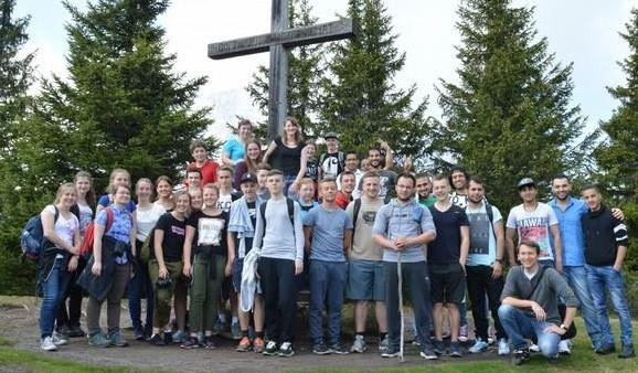 Eine Wandergruppe posiert an einem großen Holzkreuz