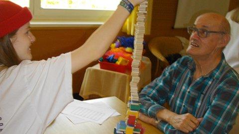 Jugendliche baut mit einem alten Mann einen Turm aus kleinen Holzbausteinen
