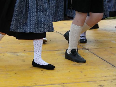 Junge und Mädchen in Trachten am Tanzen