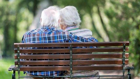 Ein älteres Ehepaar sitzt auf einer Bank im Park