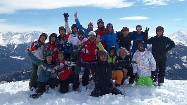 Skigruppe posiert am Berg im Schnee