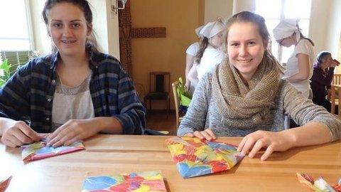 Zwei jugendliche Mädchen falten Servietten an einem Tisch