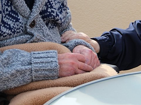 jüngere Person hält älterer die Hand