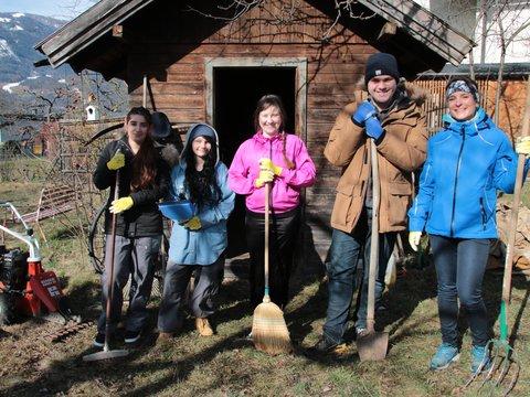 Fünf jüngere Personen haben Spaß bei der Gartenarbeit