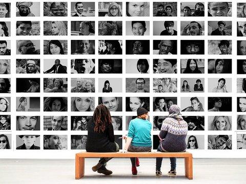 Drei Menschen in einem Museum schauen Portraits an