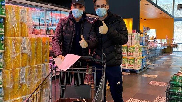 Zwei junge Männer beim Einkaufen zu Coronazeiten