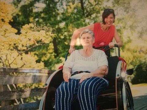 Ältere Frau im Rollstuhl wird von jüngerer Frau geschoben