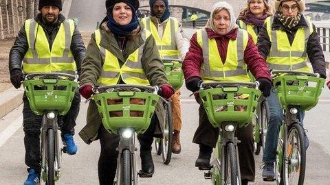 Sieben Personen mit gelben Warnwesten beim Fahrradfahren