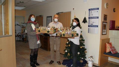 Drei Personen halten zwei Präsentkörbe mit Adventsgeschenken in Coronazeiten