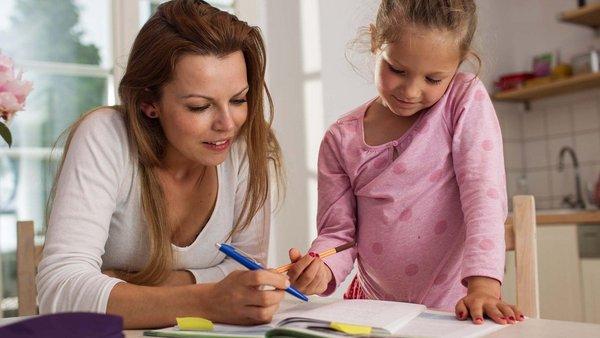 Eine Frau unterstützt ein Mädchen beim Lernen