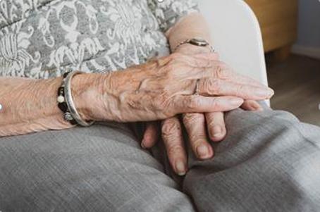 Seniorin faltet sitzend die Hände auf ihrem Schoß zusammen