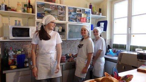 Drei Jugendliche mit weißen Schürzen und Kochhaube in einer Küche