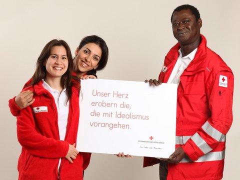 """Drei Mitarbeiter vom Österreichischen Roten Kreuz halten Schild mit der Aufschrift """"Unser Herz erobern die, die mit Idealismus vorangehen"""" in der Hand"""