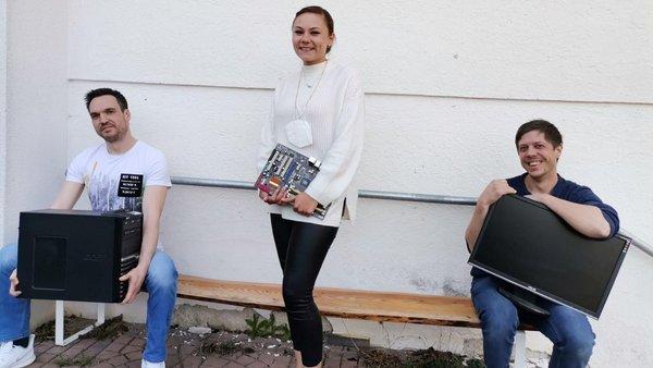 2 Männer und eine Frau halten jeweils einen Bildchirm
