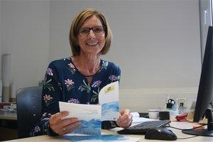 Sieglinde Breuss mit einem Heft der Freiwilligenzentren Tirol in der Hand