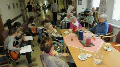 Junge Mädchen musizieren für ältere Damen und Herren