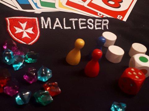 Spielfiguren und -karten auf einem Malteser-Shirt